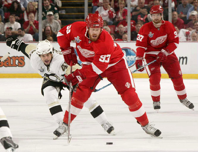 Red Wings center Johan Franzen, who set up Brian Rafalski's go-head tally, carries the puck up ice while being checked by Tyler Kennedy, who took a costly hooking penalty in the third period that led to Pavel Datsyuk's game-tying goal.
