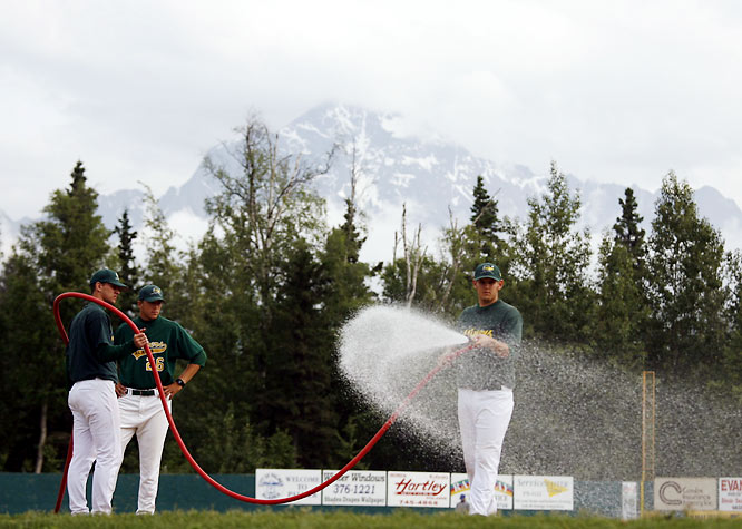 Alaskan League players typically share in the grounds-keeping duties at their parks, and at right, Michigan State pitcher Chris Cullen -- who had a 1.74 ERA for Mat-Su in 2007 -- waters Hermon Brothers Field before a June game. Some Miners players take day jobs with the team, doing everything from cleaning bathrooms to taking on laundry duty.
