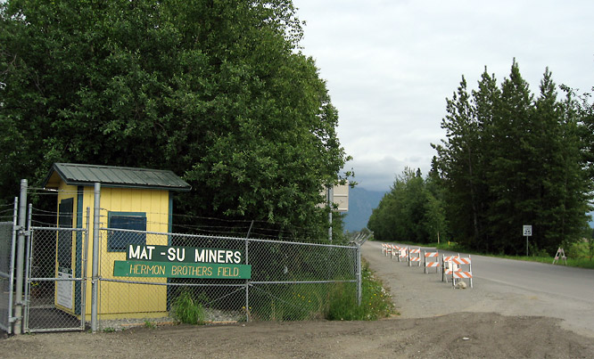 Hermon Brothers Field is somewhat of a hidden gem, located off a dirt road adjacent to the Alaska State Fairgrounds. The field's entrance is marked only by a chain-link fence and this wooden sign. Miners fans park well beyond Hermon Brothers' centerfield fence and then make the long walk to the grandstand.