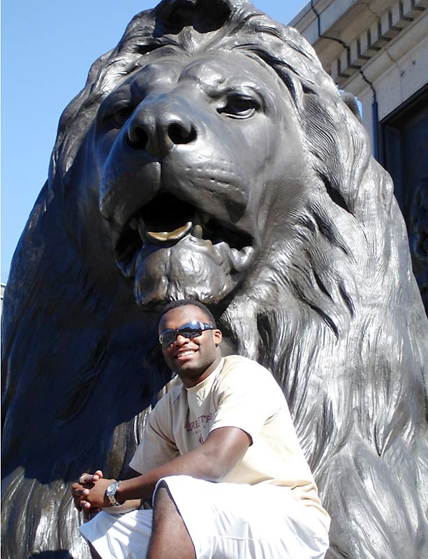 Here, Rolle stands in front of a lion in Trafalgar Square in London.
