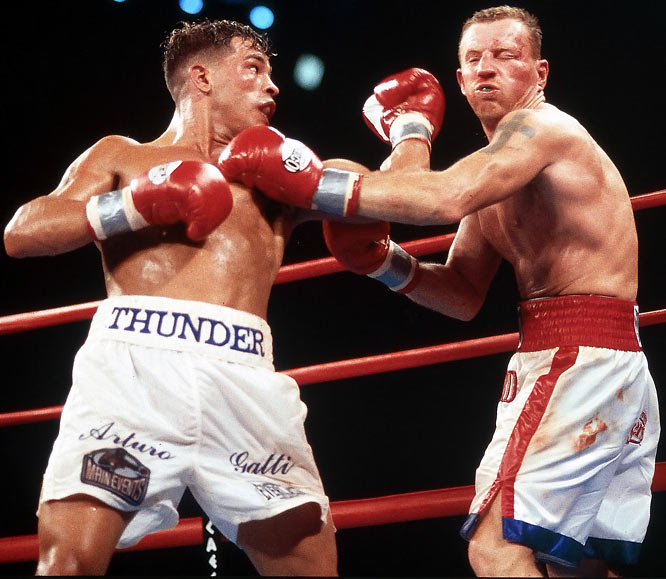 "In perhaps the most brutal trilogy of fights in boxing history, Ward and Gatti split a pair of bouts in 2002 before staging an epic final battle. At the June 2003 fight, both faces were bloody, Gatti rebroke his right hand in the fourth round and was knocked to the canvas in the sixth, but came out on top in the scoring. Gatti-Ward I and Gatti-Ward III were named ""Fight of the Year"" by Ring Magazine in 2002 and 2003, respectively."