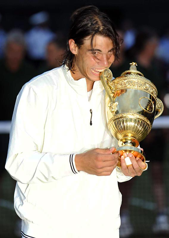 Amid the darkness of the postmatch ceremonies, Rafael Nadal hams it up for the photographers by taking a bite out of the Wimbledon Trophy.