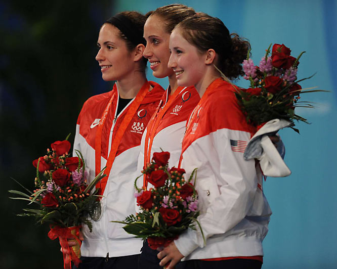 Fencer Mariel Zagunis of the U.S. (center) stands at the podium with compatriots Sada Jacobson (left) and Becca Ward after winning gold, silver and bronze respectively.