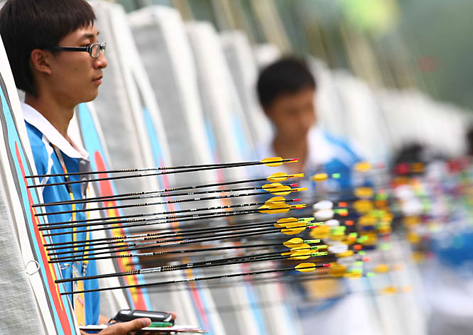 An Olympic volunteer keeps a watchful eye on the women's archery competition.