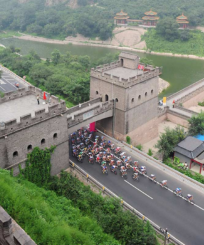 Men's road cyclists go under the Great Wall.