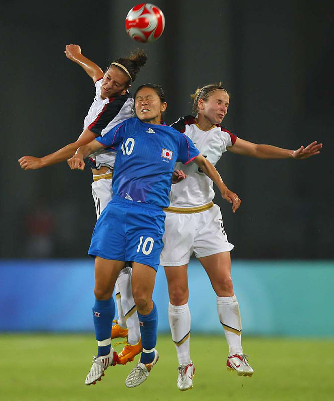 Homare Sawa of Japan is surrounded by Carli Lloyd (left) and Lindsay Tarpley of the U.S.