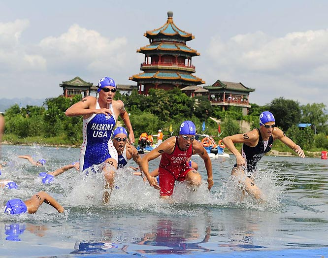 Sarah Haskins (42) and Laura Bennett (40) of the U.S. compete against Switzerland's Magali di Marco in the finals of the triathlon.