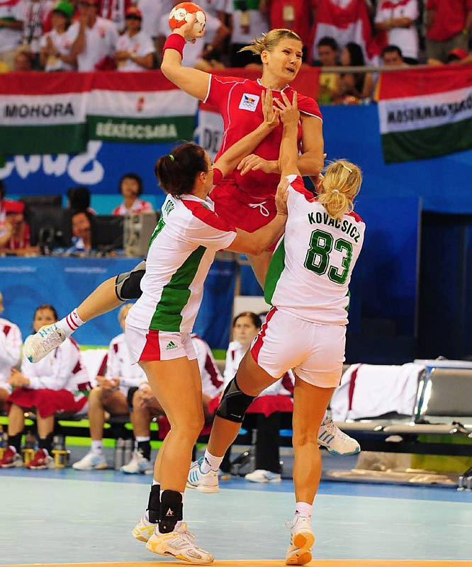 Carmen Amariei of Romania battles Hungary's Timea Toth (17) and Monika Kovacsicz (83), but Hungary went on to beat Romania 34-30 in the quarterfinals of the team handball competition.