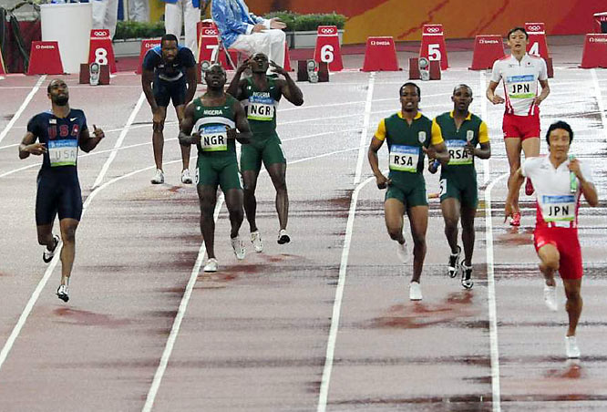 Tyson Gay (far left) pulls up after he and Darvis Patton botched their relay handoff in the 4 x 100 relay.
