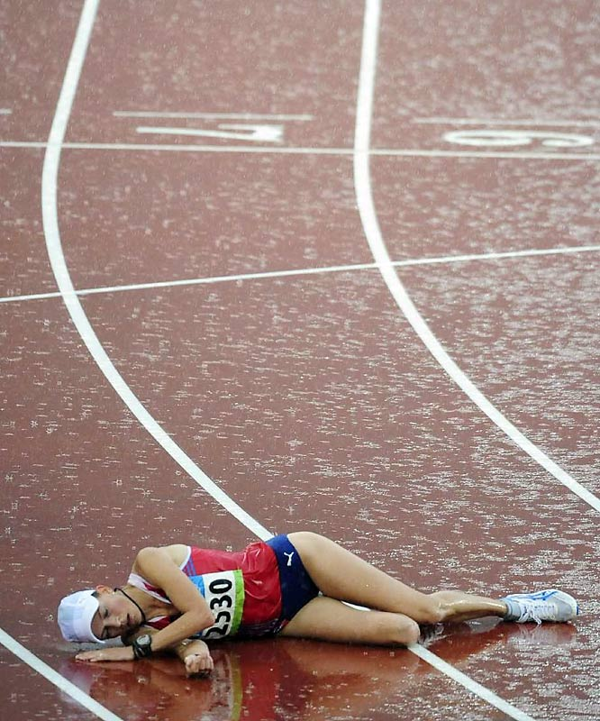 Kjersti Tysse Platzer of Norway collapses after winning the silver in the 20km walk.