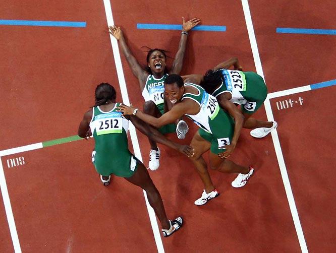 Franca Idoko of Nigeria celebrates with teammates Oludamola Osayomi (2512), Halimat Ismaila (2523) and Gloria Kemasuode (2514) after the 4 x 100 relay.