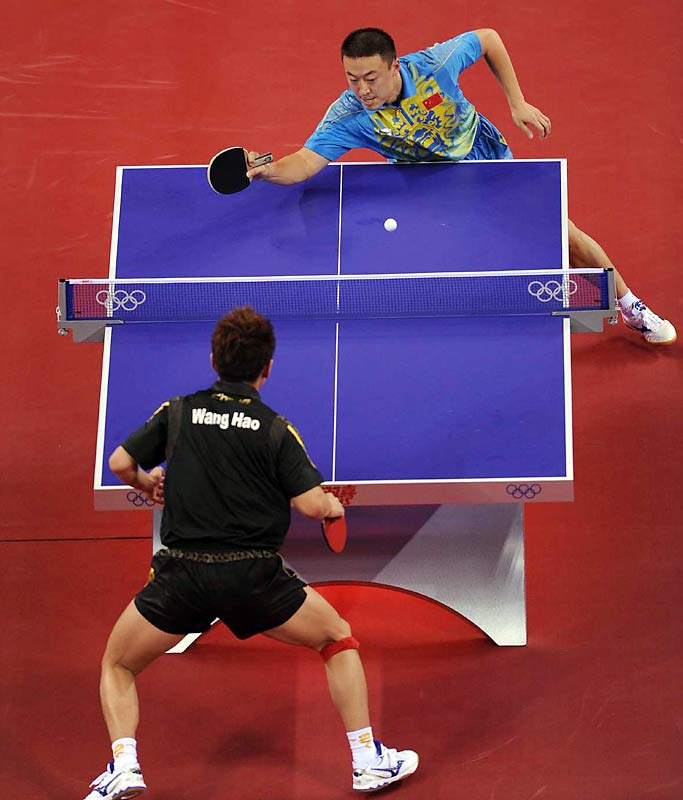 Ma Lin (in blue) and Wang Hao, both of China, compete in the singles gold medal match.