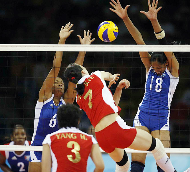 Cuba's Zoila Barros (18) and Daimi Ramirez attempt to block Zhou Suhong in a preliminary round match. Cuba won 18-25, 14-25, 25-23, 32-30, 15-13.