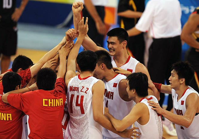 Yao Ming of China huddles up with his team during the preliminary game against Germany. He led all scorers with 25 points in his team's 59-55 victory.