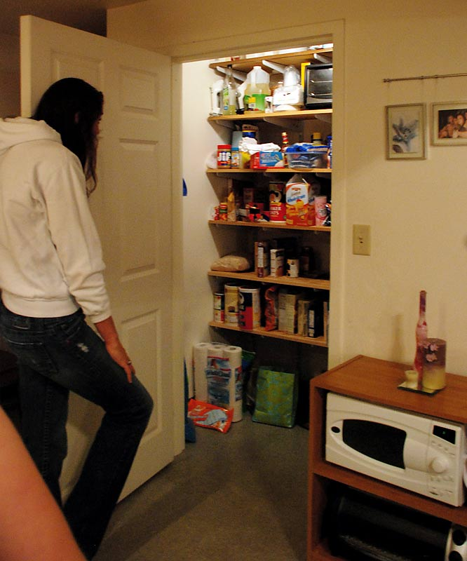 "Brown contemplates the labeling of snacks in her walk-in pantry after seeing a box of whole grain cheddar gold fish (third shelf). ""They were the only ones the [grocery store] had,"" Brown said, defending her choice. She questioned aloud why labels advertise their healthy ingredients. ""Do you ever see foods say they have trans fat?"" she asked."