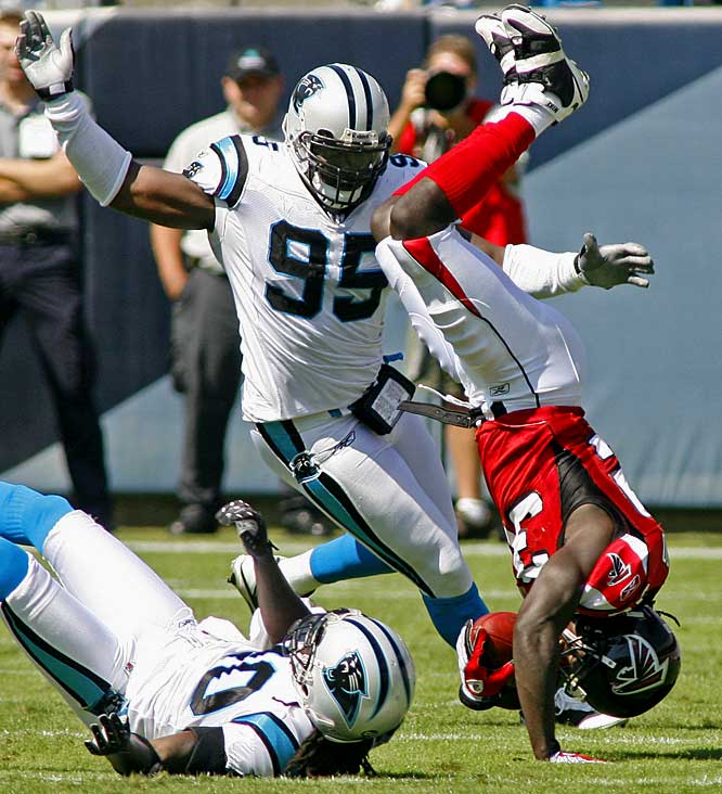 Jerious Norwood is upended by Panthers cornerback Chris Gamble (20) and defensive end Charles Johnson (95) in the first half of Atlanta's 24-9 loss to Carolina.