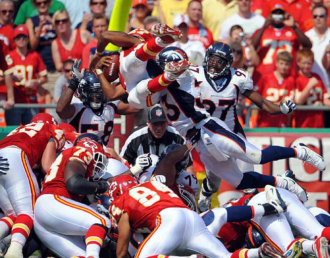 Larry Johnson dives to the goal line past Broncos safety Marquand Manuel (33) and linebacker Boss Bailey (97) in the second quarter. LJ, two weeks after complaining that he was being phased out, ran for 198 yards and two touchdowns to lead the previously winless Chiefs past the previously unbeaten Broncos 33-19, snapping a franchise-record 12-game losing streak.