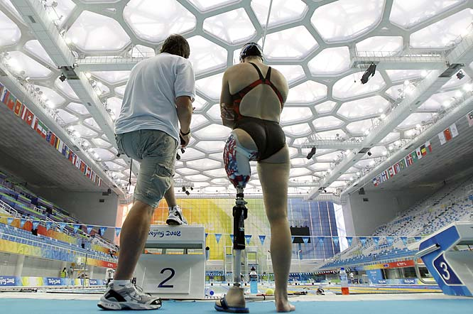 Melissa Stockwell of the U.S. chats with coach Jimi Flowers during a team training session. Stockwell is one of two veterans competing who were injured in Iraq.