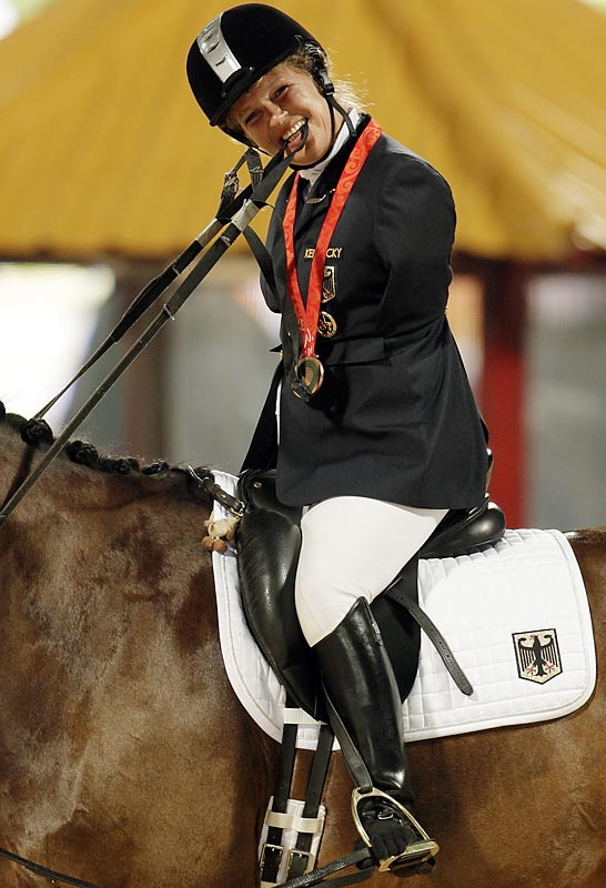Bronze medalist Bettina Eistel of German celebrates after winning the Equestrian Individual Dressage Championship Test Grade III.