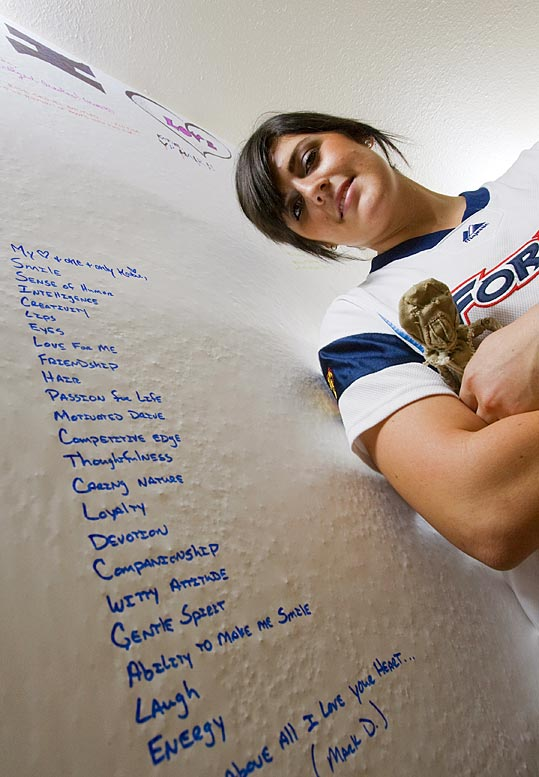 "Burkhart poses next to her ""I love your ..."" wall, where house guests can write their favorite things about anyone else. She's standing next to a laundry list of things her boyfriend, Mark, wrote for her."