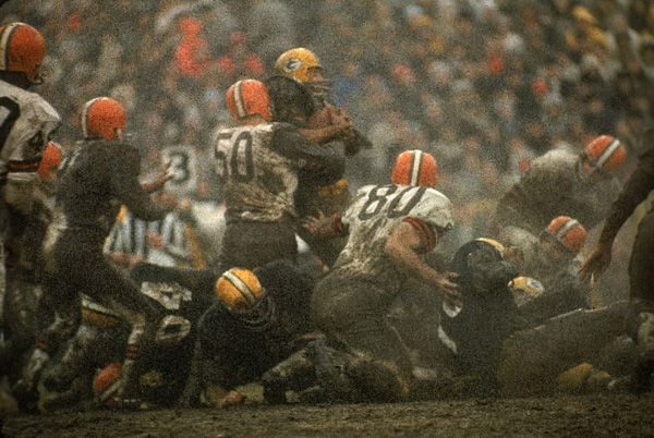 Vince Costello of the Cleveland Browns has Jim Taylor of the Green Bay Packers in a bear hug during play on muddy Lambeau Field. The Pack, under legendary coach Vince Lombardi, would eventually emerge victorious, 23--12, gaining its ninth NFL title.