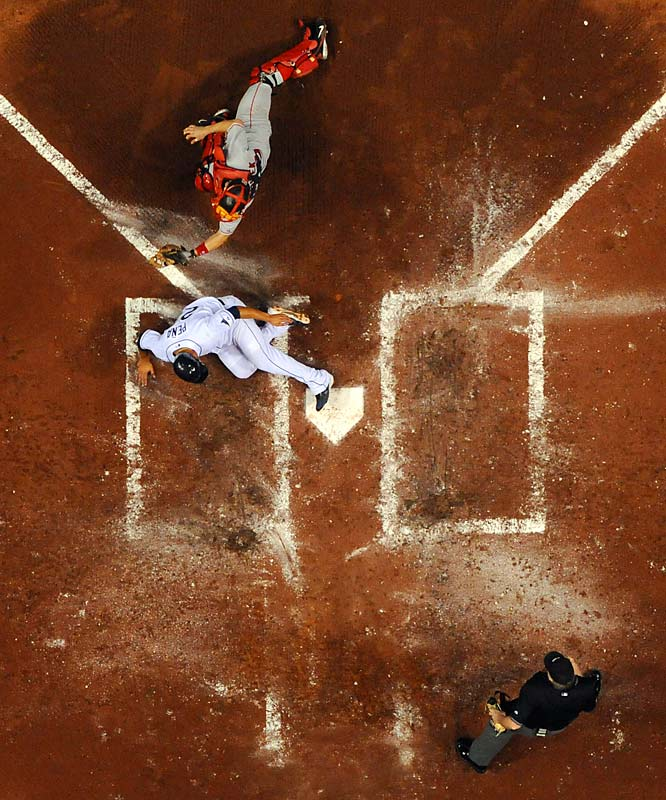 Just ahead of the tag by Jason Varitek, Carlos Pena scores the tying run on a fourth inning double by Evan Longoria. The Rays' third baseman hit four home runs in the series, driving in eight runs.