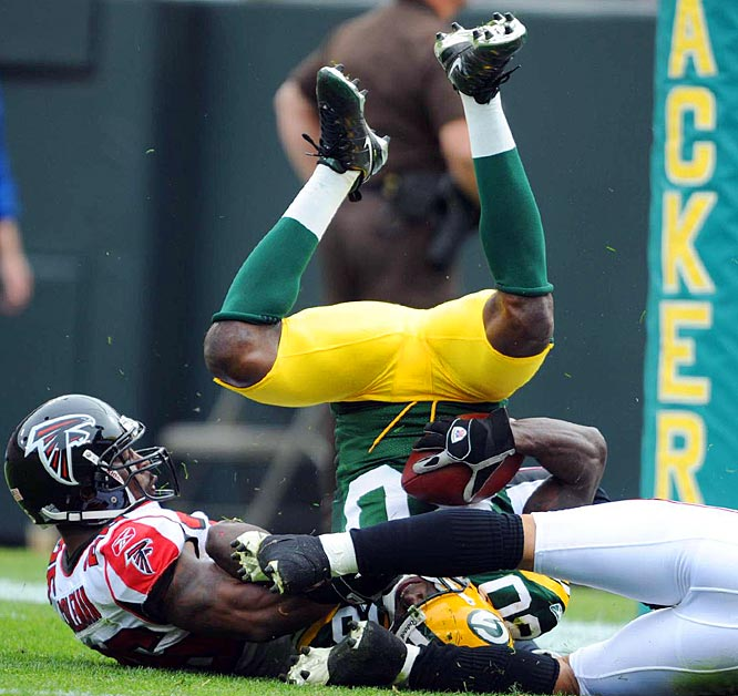 Donald Driver lands upside-down in the end zone as he hauls in a 44-yard touchdown reception in the second quarter.  The Packers lost 27-24 to the Falcons.