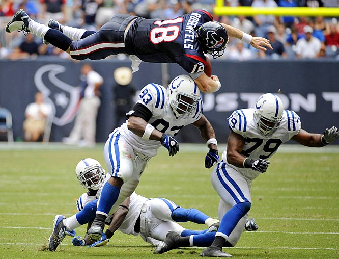 Texans QB Sage Rosenfels flies over Colts defensive end Dwight Freeney (93) after being hit by Raheem Brock (79) during the fourth quarter.  Rosenfels fumbled the ball and the Colts returned it 68 yards for a touchdown.