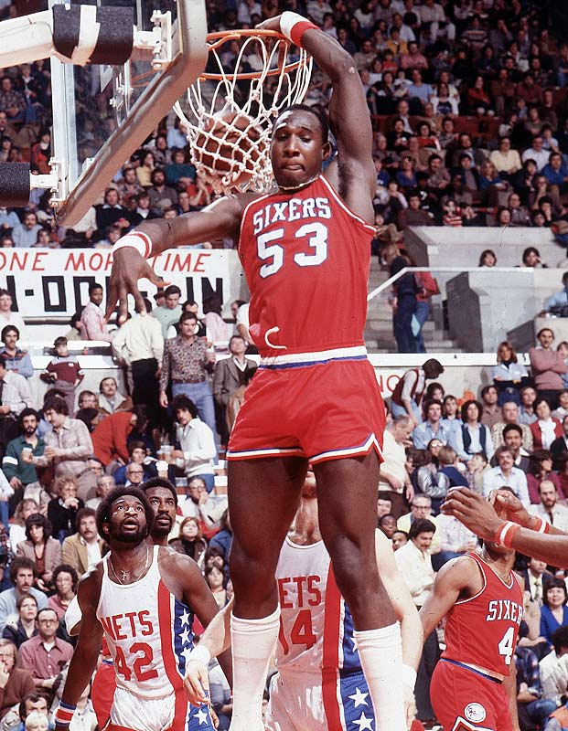 While playing center for Philadelphia, Darryl Dawkins shatters a backboard with a slam dunk during the Sixers' 110-103 loss at Kansas City.