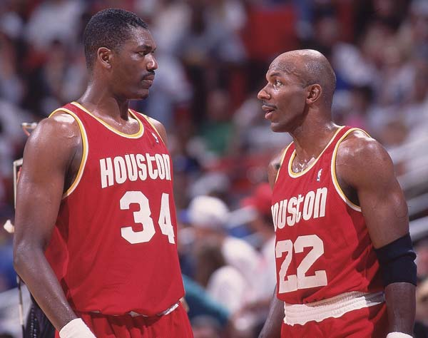 Houston's Hakeem Olajuwon (pictured here with Clyde Drexler) scores 21 points in the Rockets' 119-97 victory over visiting Minnesota, becoming the ninth NBA player to collect 20,000 points and 10,000 rebounds in a career.