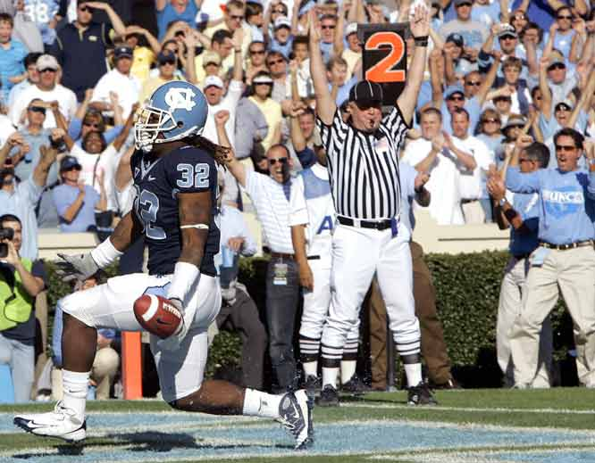 Ryan Houston (left) ran for a pair of fourth-quarter touchdowns and Cam Sexton tossed two more  to help the Tar Heels clinch their first winning season in seven years.