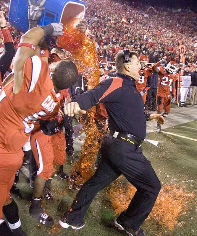 Utah coach Kyle Whittingham tries to escape a Gatorade shower after his team put the finishing touches on a 12-0 regular season. Up next: A likely berth in a BCS bowl.