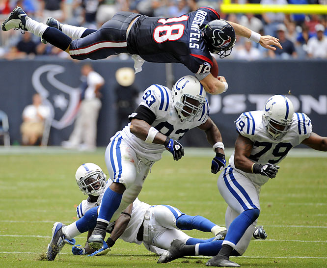 Houston quarterback Sage Rosenfels flies over Indianapolis defensive end Dwight Freeney (93) after being hit by Raheem Brock (79) while trying to pick up extra yardage. Rosenfels fumbled the ball and the Colts returned it for a touchdown en route to a 31-27 victory.