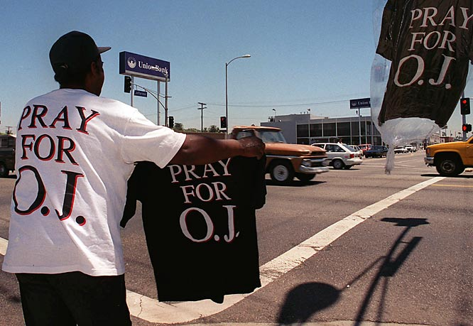 "Simpson was eventually caught and put on trial for the murders. The American public soon became enthralled with the case. In this photo from June 1994, a California man peddles his ""Save O.J."" T-shirts on a street corner in the Crenshaw section of Los Angeles."