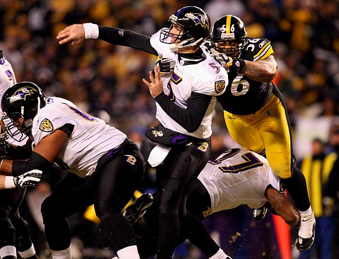 Joe Flacco gets a pass off as Steelers' linebacker LaMarr Woodley leaps to make the hit in the second quarter.