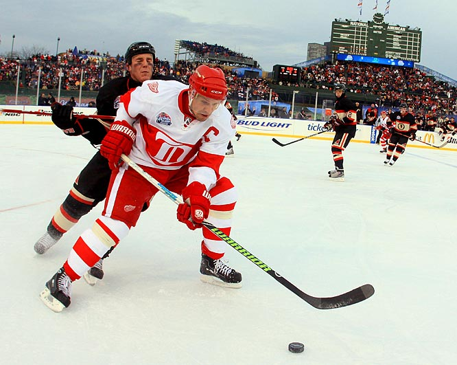 "Nicklas Lidstrom fights for the puck with defenseman James Wisniewski.  Regarding the outdoor game, Lidstrom said ""It exceeded my expectations."""