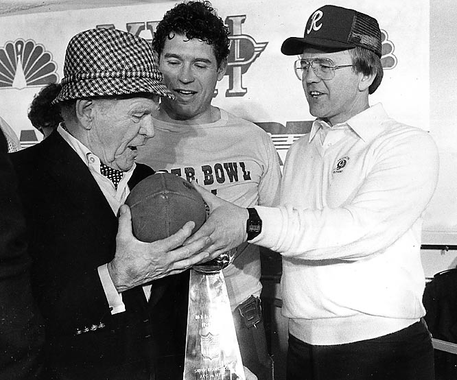 Washington owner Jack Kent Cooke, running back John Riggins and head coach Joe Gibbs share the game ball in the locker room after the Redskins' 27-17 win over Miami in Super Bowl XVII.