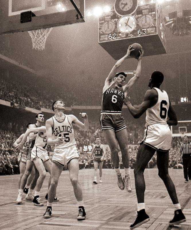 Tommy Heinsohn (No. 15) and Bill Russell (No. 6) watch as St. Louis Hawk forward Cliff Hagen grabs a rebound during the 1957 NBA Championship. The Celtics won the series in seven games.