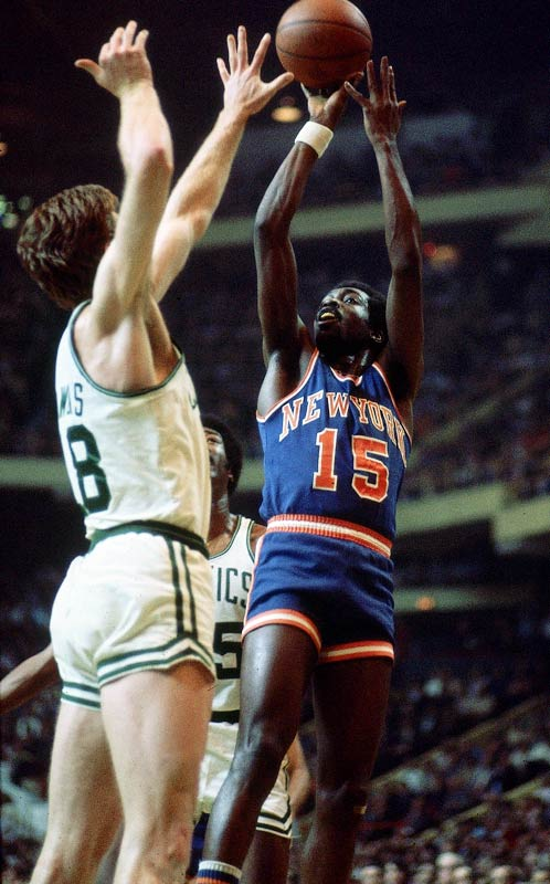 Earl Monroe lofts a shot over the extended hand of Dave Cowens during a game against the Celtics.