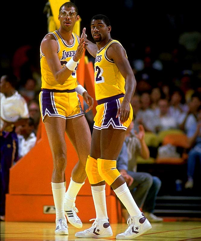 Magic Johnson and Kareem Abdul-Jabbar exchange a high five during a game against Portland.