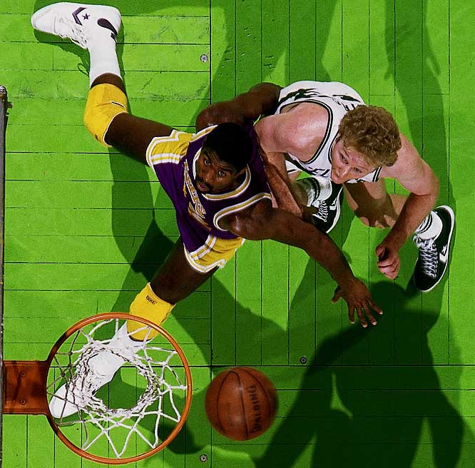 Longtime rivals Magic Johnson and Larry Bird battle for a rebound.