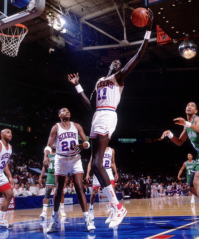 Manute Bol uses all of his 7-feet-7-inches to grab a rebound against Dallas.