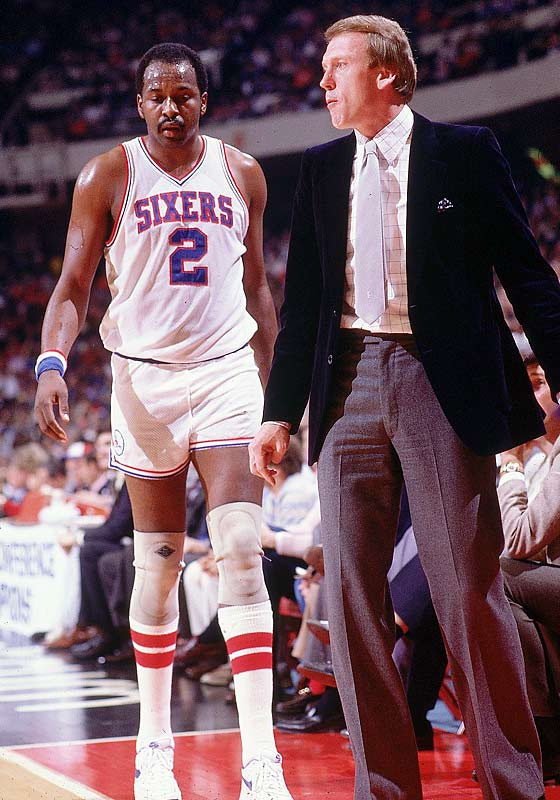 Moses Malone retreats to the bench as coach Billy Cunningham looks on.
