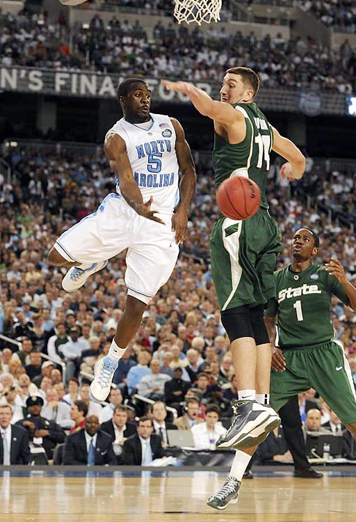 North Carolina guard Ty Lawson dishes a pass around Goran Sutton of Michigan State during the Tar Heels' 89-72 victory at Ford Field in Detroit.
