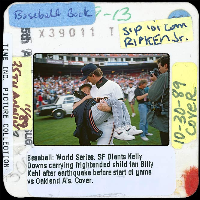 "In an image that was used on the cover of the SI issue headlined ""The Day The World Series Stopped,"" Giants pitcher Kelly Downs carries his nephew to safety. An earthquake that struck just before game 3 halted the Series between San Francisco and Oakland for 10 days. This image also was used in a Cal Ripken Jr. commemorative issue years later."