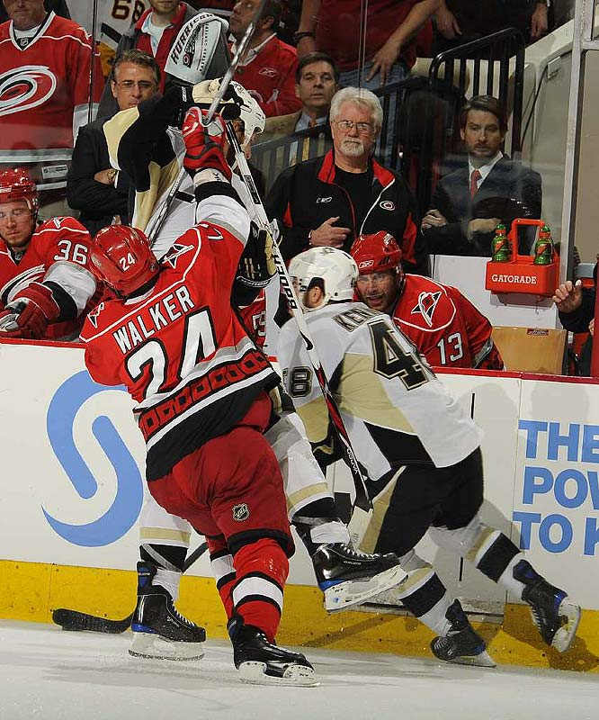 Carolina's Scott Walker gets a bruising check as the Pens' Tyler Kennedy (48) comes in to assist. The Hurricanes will look to avoid the sweep when it plays host to the Pens Tuesday night.