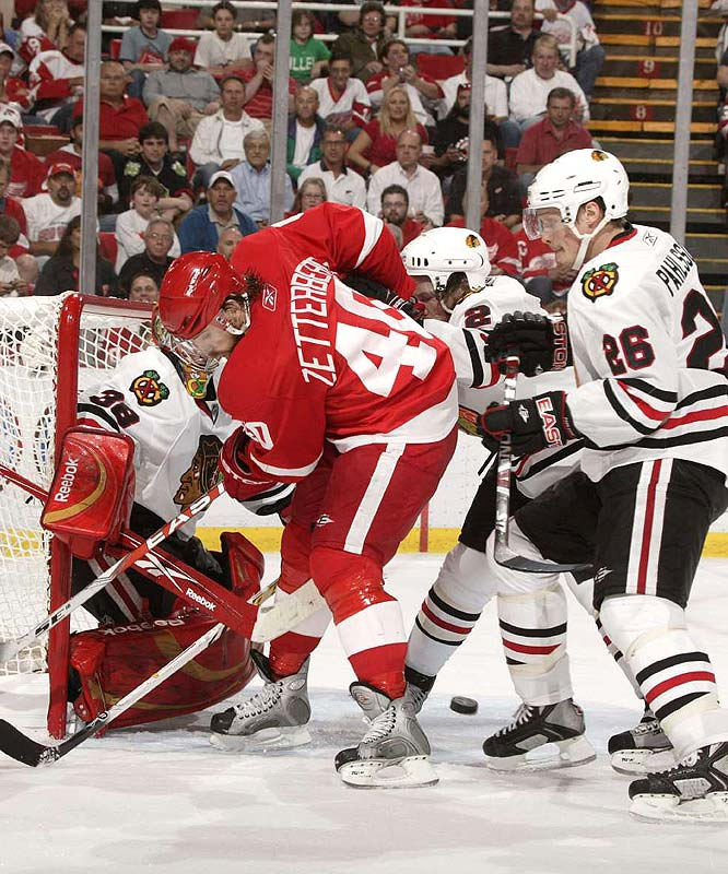 Henrik Zetterberg (40) has his work cut out for him as he tries to get the puck past Chicago's Cristobal Huet (38), Duncan Keith (2) and Samuel Pahlsson (26) during Game 5 of the Western Conference finals. Darren Helm's overtime goal lifted the Red Wings into the Stanley Cup finals -- and a rematch against Pittsburgh -- with a 2-1 win.