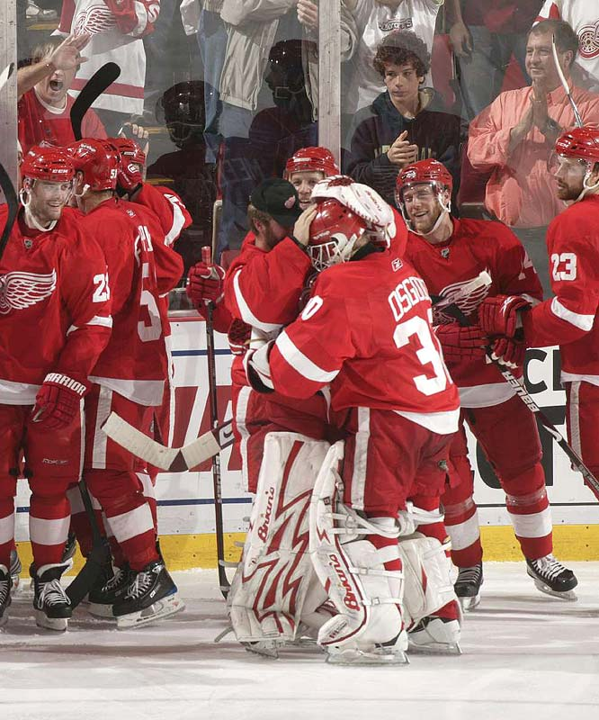 Red Wing teammates congratulate goalie Chris Osgood (center) after Detroit eliminated Chicago four games to one in the Western Conference finals.