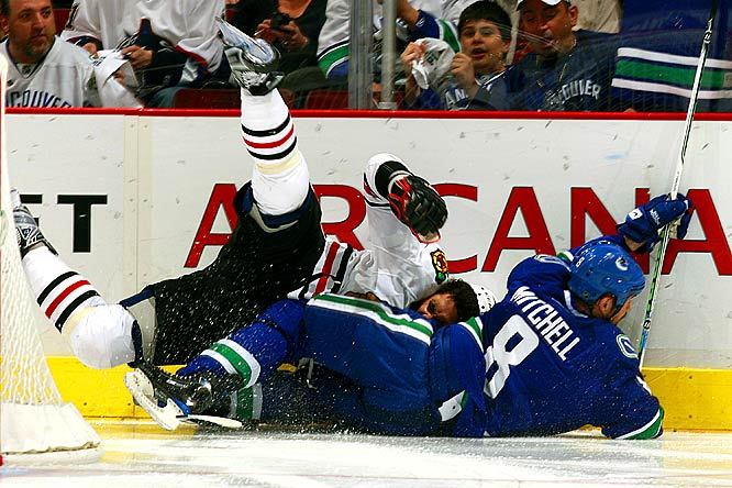 Canucks defenseman Willie Mitchell takes down Blackhawks forward Dustin Byfuglien along the boards during Game 2.