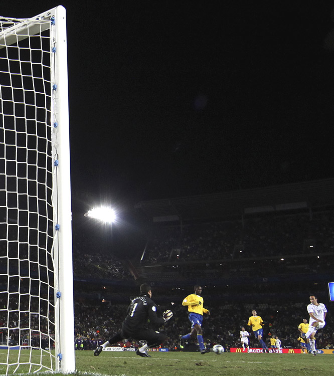 USA's Landon Donovan (right) uses his left foot to drive the ball past Brazilian keeper Julio Cesar (left) and into the net. The goal, which came in the 27th minute, gave the U.S. a 2-0 advantage.